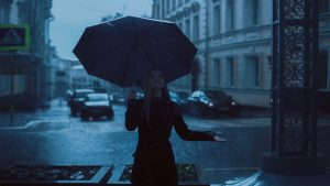 woman in black with umbrella under the rain