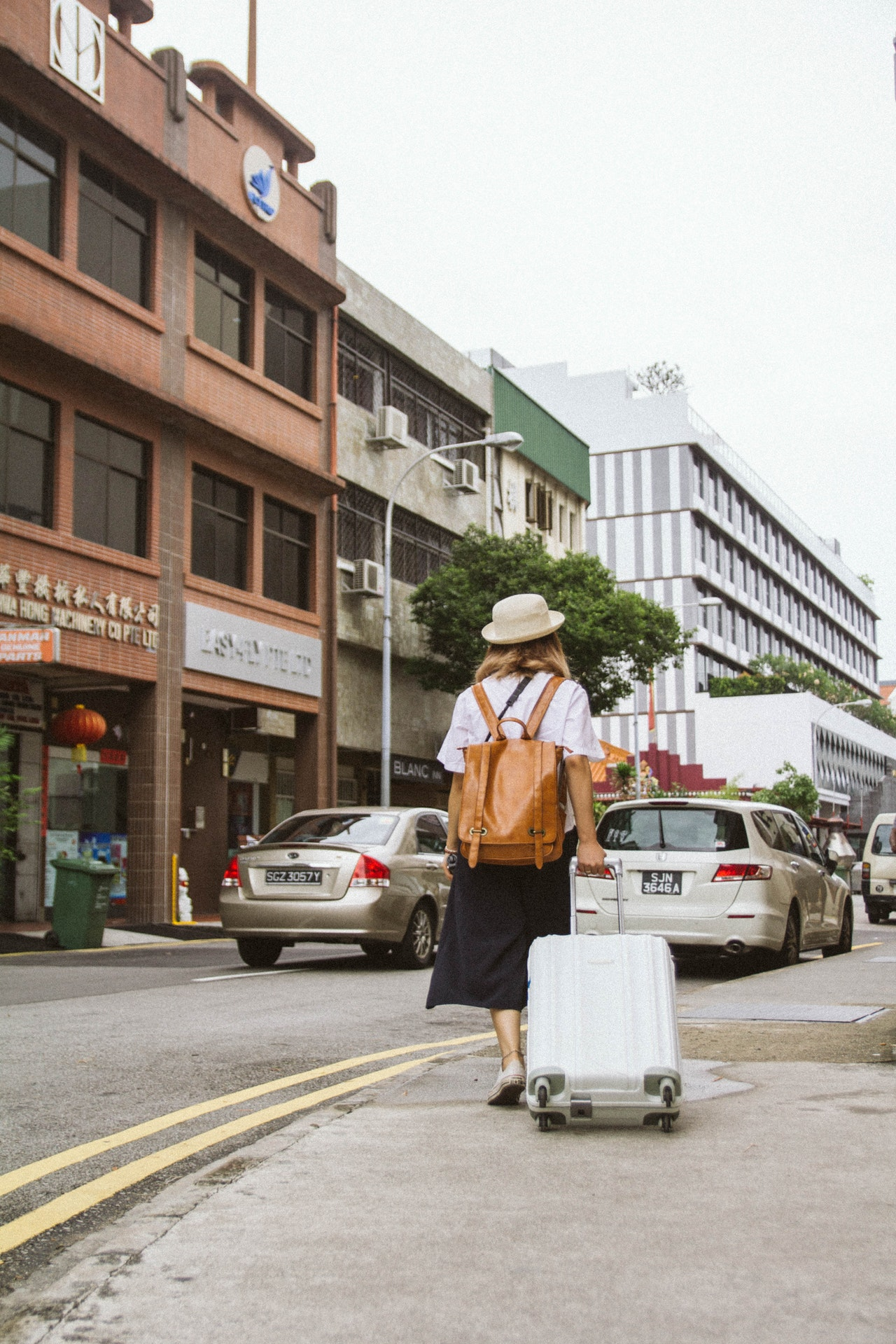 hard shell suitcase carried by a woman traveling
