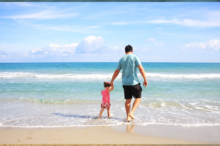 the father and daughter walking in the beach
